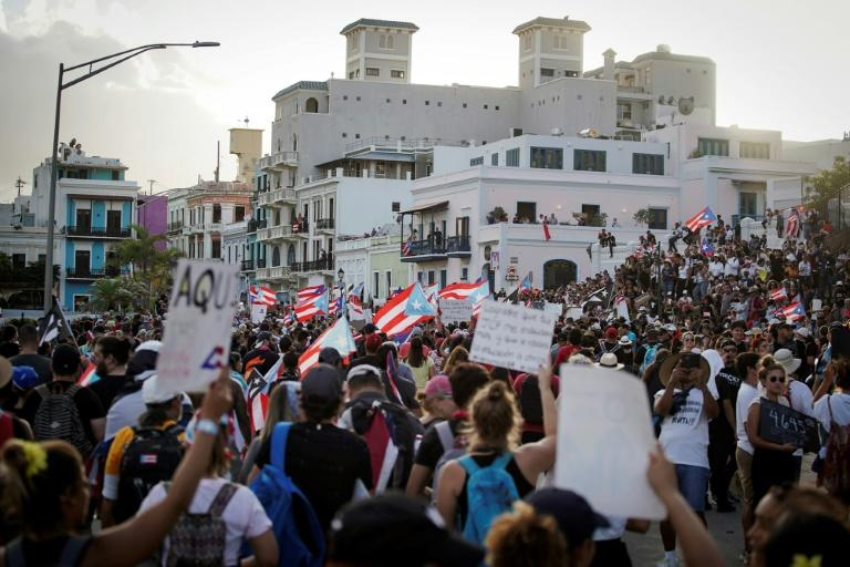 People take part of a demostration in San Juan, Puerto Rico demanding Governor Ricardo Rossello's resignation following corruption accusations and the leak of sexist and homphobic text messages (AFP Photo/eric rojas)