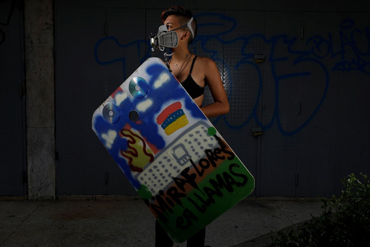 """<p>A demonstrator holding a rudimentary shield that reads """"Miraflores on fire,"""" poses for a picture before a rally against Venezuelan President Nicolas Maduro's government in Caracas, Venezuela, May 24, 2017. She said: """"I'm protesting because Venezuela is beautiful and it's sad that everyone has to go. I fight because I don't want to leave Venezuela, I want to grow here."""" (Photo: Carlos Garcia Rawlins/Reuters) </p>"""