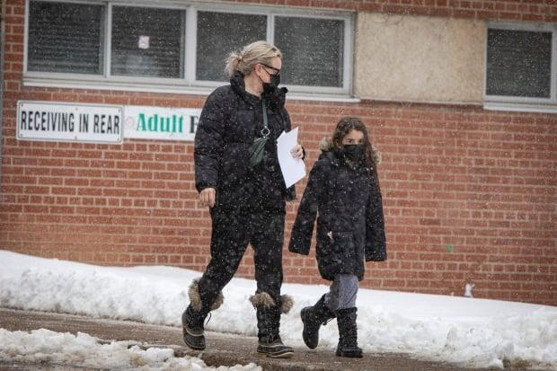 Students and families pick up take-home COVID-19 test kits at John Polanyi Collegiate Institute in Toronto last week. Testing of asymptomatic students is expanding across Ontario. (Evan Mitsui/CBC - image credit)