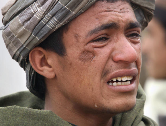 An Afghan youth mourns for relatives, who were allegedly killed by a U.S. service member in Panjwai, Kandahar province south of Kabul, Afghanistan, Sunday, March. 11, 2012. A U.S. service member walked out of a base in southern Afghanistan before dawn Sunday and started shooting Afghan civilians, according to villagers and Afghan and NATO officials. Villagers showed an Associated Press photographer 15 bodies, including women and children, and alleged they were killed by the American. (AP Photo/Allauddin Khan)
