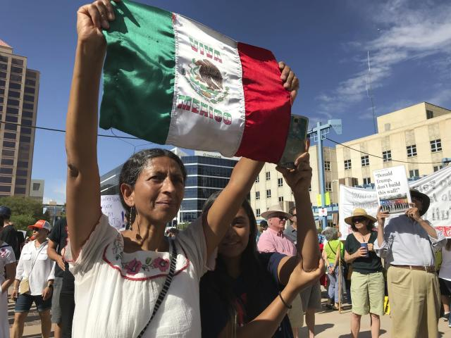 <p>Margarita Perez of Albuquerque, with her daughter by her side, holds up a Mexican flag during a protest on Civic Plaza in Albuquerque, N.M., on Saturday, June 30, 2018. Perez was among thousands who gathered on the plaza to voice their opposition to U.S. immigration policies and President Donald Trump. (Photo: Susan Montoya Bryan/AP) </p>