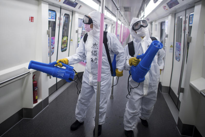 In this March 23, 2020 photo released by Xinhua News Agency, workers disinfect a subway train in preparation for the restoration of public transport in Wuhan, in central China's Hubei province. China's health ministry says Wuhan has now gone several consecutive days without a new infection, showing the effectiveness of draconian travel restrictions that are slowly being relaxed around the country. (Xiao Yijiu/Xinhua via AP)