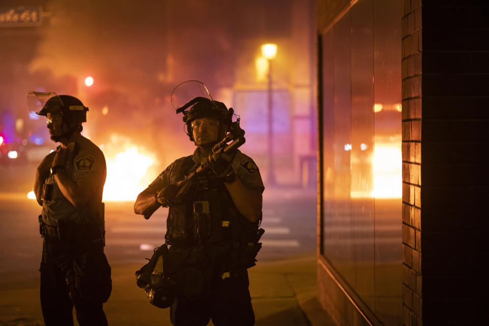 Police stand guard after protesters set fire to dumpsters after a vigil was held for Winston Boogie Smith Jr. early on Saturday, June 5, 2021. Authorities say Smith, wanted on a weapons violation, fired a gun from inside his vehicle before he was fatally shot by members of a federal task force as they were trying to arrest him. (AP Photo/Christian Monterrosa)
