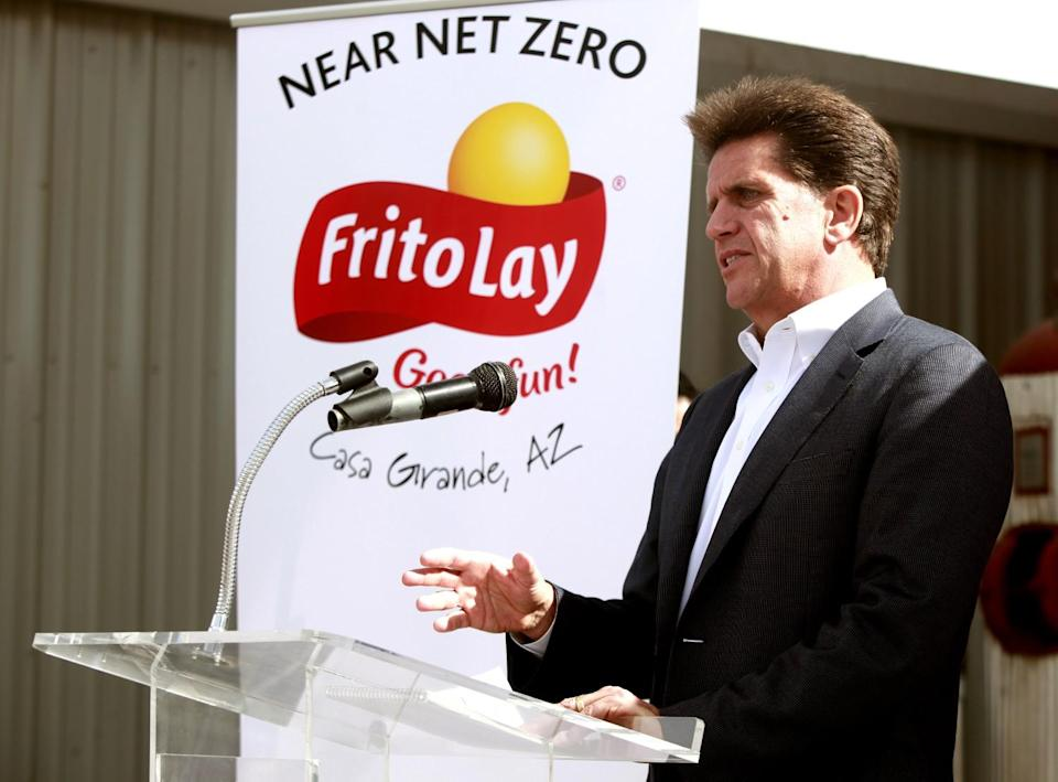 Al Carey speaks at a lectern in front of a sign with Frito-Lay's logo that says Near net zero