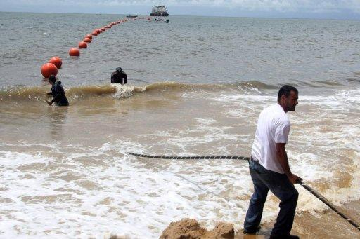 Technicians display the ACE submarine fiber optic cable on the shore of Libreville, Gabon, in 2011