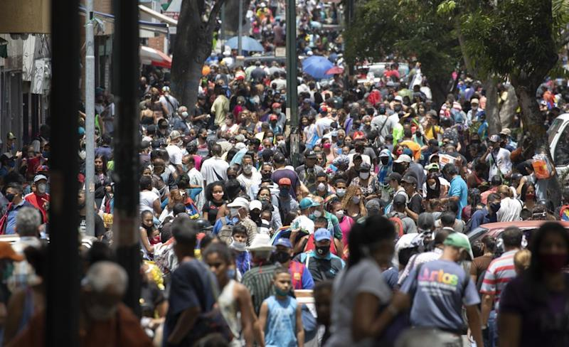 People, some wearing face masks as a measure to curb the spread of the new coronavirus, walk in the Catia neighborhood of Caracas, Venezuela. Source: AP