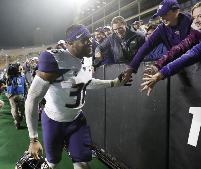"Washington linebacker Azeem <a class=""link rapid-noclick-resp"" href=""/soccer/players/victor-384941"" data-ylk=""slk:Victor"">Victor</a> is congratulated by fans as he leaves the field after the team's NCAA college football game against Colorado on Saturday, Sept. 23, 2017, in Boulder, Colo. Washington won 37-10. (AP Photo/David Zalubowski)"