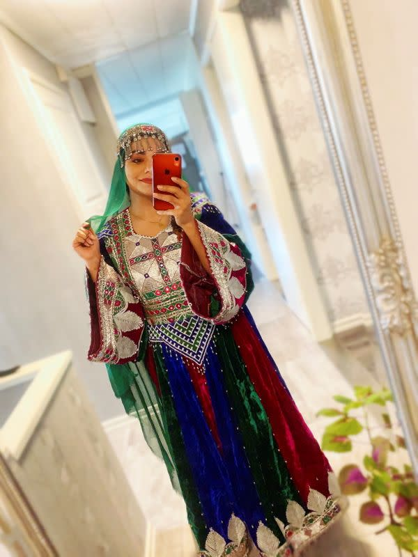 A woman poses in traditional Afghan attire, in Stockholm