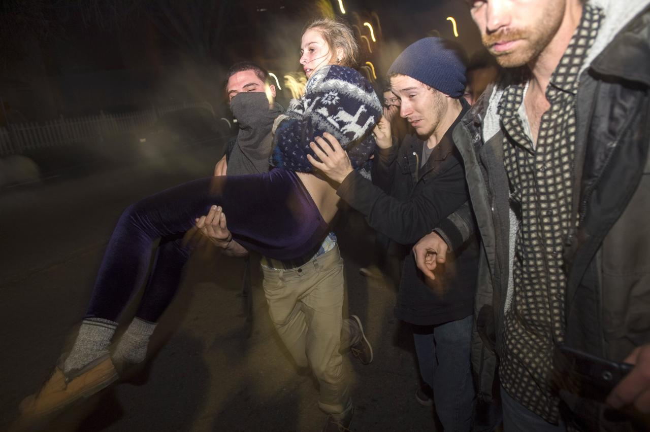 Protesters carry a fellow demonstrator as police officers deploy teargas during a protest against police violence in the U.S., in Berkeley, California early December 7, 2014. REUTERS/Noah Berger  (UNITED STATES - Tags: CIVIL UNREST)