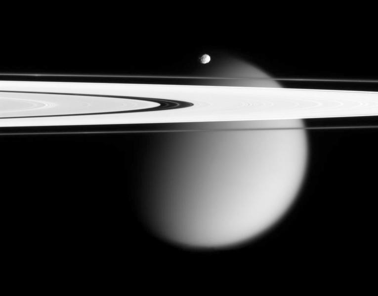 This image made by the Cassini spacecraft and provided by NASA on March 12, 2006, shows two of Saturn's moons, the small Epimetheus and smog-enshrouded Titan, with Saturn's A and F rings stretching across the frame. Launched in 1997, Cassini reached Saturn in 2004 and has been exploring it from orbit ever since. Cassini's fuel tank is almost empty, so NASA has opted for a risky, but science-rich grand finale. (AP Photo/NASA)
