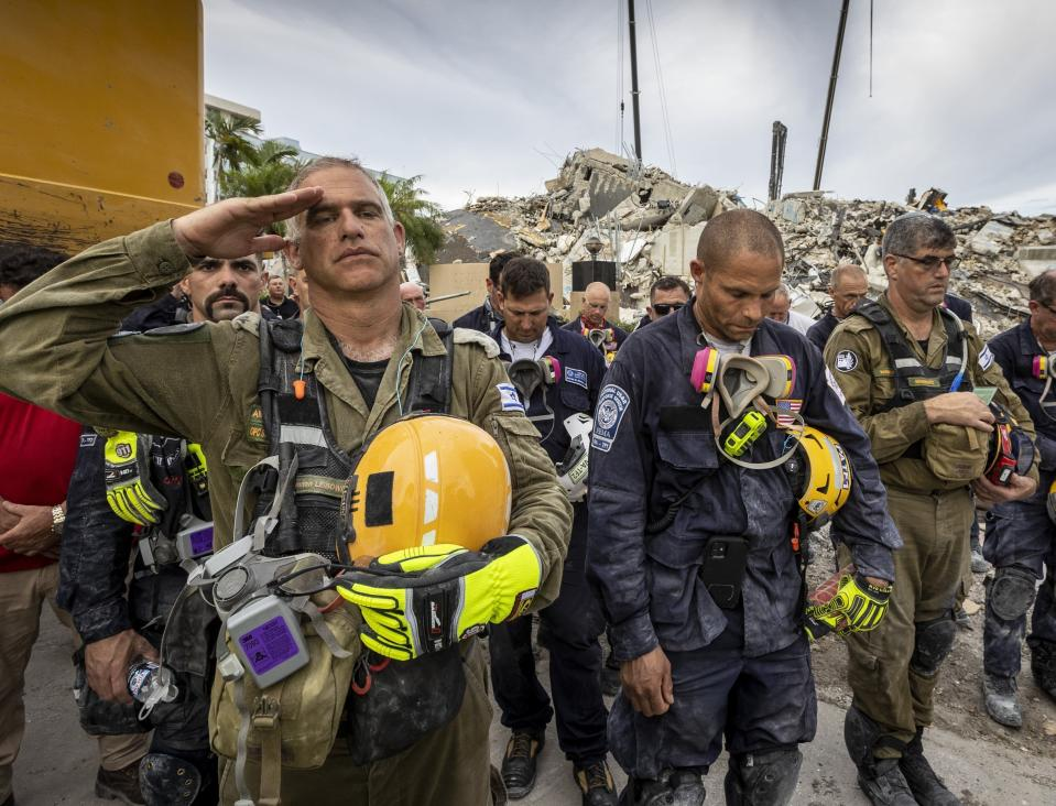 """FILE - A member of the Israeli search and rescue team, left, salutes in front of the rubble that once was Champlain Towers South during a prayer ceremony, Wednesday, July 7, 2021, in Surfside, Fla. The Israeli search and rescue team that arrived in South Florida shortly after the Champlain Towers South collapsed last month is heading home after an emotional sendoff in Surfside. The team planned to leave Florida on Sunday, July 11. During a brief Saturday evening ceremony, Miami-Dade Mayor Daniella Levine Cava thanked the battalion for their """"unrelenting dedication."""" (Jose A Iglesias/Miami Herald via AP)"""
