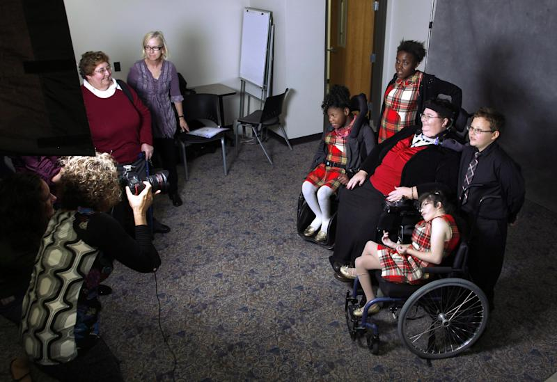 In this Nov. 14, 2012 photo, Carrie Ann Lucas, third from right, sits with her adopted children for a photograph by volunteer photographer Jill Kaplan, left, during a party celebrating National Adoption Day at the Arapahoe County Justice Center in Centennial, Colo. Lucas says she's had to deal with several investigations by child welfare officials that she attributed to bias linked to her disabilities. (AP Photo/Brennan Linsley)