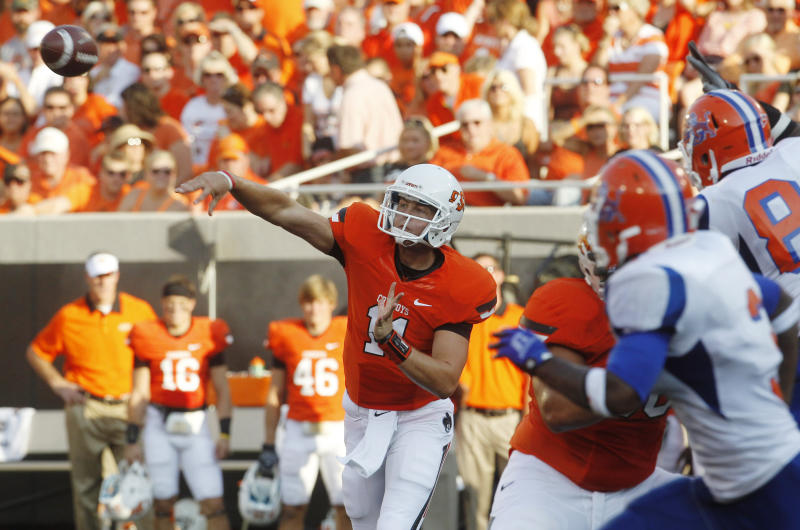 Oklahoma State quarterback Wes Lunt, left, passes under pressure from Savannah State in the first quarter of an NCAA college football game in Stillwater, Okla., Saturday, Sept. 1, 2012. (AP Photo/Sue Ogrocki)