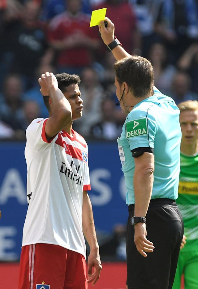 Soccer Football - Bundesliga - Hamburger SV v Borussia Moenchengladbach - Volksparkstadion, Hamburg, Germany - May 12, 2018 Hamburg's Douglas Santos is shown a yellow card by referee Felix Brych REUTERS/Fabian Bimmer DFL RULES TO LIMIT THE ONLINE USAGE DURING MATCH TIME TO 15 PICTURES PER GAME. IMAGE SEQUENCES TO SIMULATE VIDEO IS NOT ALLOWED AT ANY TIME. FOR FURTHER QUERIES PLEASE CONTACT DFL DIRECTLY AT + 49 69 650050