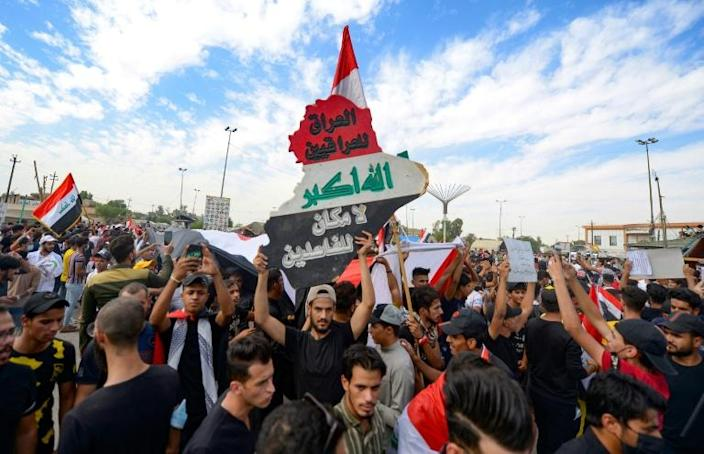 """Iraqi protesters mark the first anniversary of a massive anti-government movement demanding the ouster of the ruling class in the southern city of Najaf. The words in Arabic read: """"Iraq belongs to the Iraqis, no room for the corrupt"""""""
