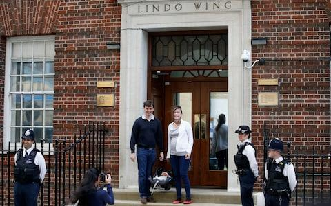 Police officers watch as a couple pose for a photo while holding a baby outside the Lindo Wing - Credit: HENRY NICHOLLS /Reuters