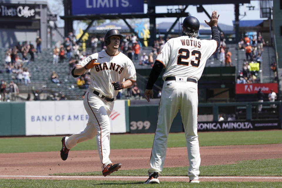 San Francisco Giants' Alex Dickerson, left, is congratulated by third base coach Ron Wotus, right, after hitting a solo home run against the Colorado Rockies during the first inning of a baseball game in San Francisco, Sunday, April 11, 2021. (AP Photo/Jeff Chiu)