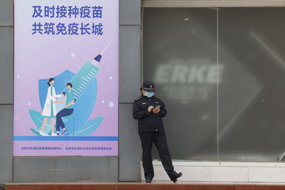 """A uniformed worker stands outside a coronavirus vaccination site with a board displaying the slogan, """"Timely vaccination to build the Great Wall of Immunity together"""" in Beijing on Friday, April 9, 2021. China's success at controlling the outbreak has resulted in a population that has seemed almost reluctant to get vaccinated. Now it is accelerating its inoculation campaign by offering incentives — free eggs, store coupons and discounts on groceries and merchandise — to those getting a shot. (AP Photo/Ng Han Guan)"""