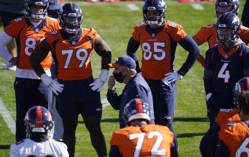 Denver Broncos head coach Viuc Fangio, center, talks with players before they take part in drills during an NFL football practice Wednesday, Oct. 28, 2020, at the team's headquarters in Englewood, Colo. (AP Photo/David Zalubowski)