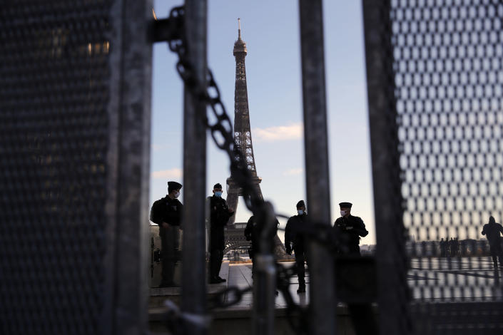 Policemen stand guard behind a security fence during a protest against bill on police images, in Paris, Saturday, Nov. 21, 2020. Thousands of people took to the streets in Paris and other French cities Saturday to protest a proposed security law they say would impinge on freedom of information and media rights. The Eiffel tower is seen background. (AP Photo/Christophe Ena)