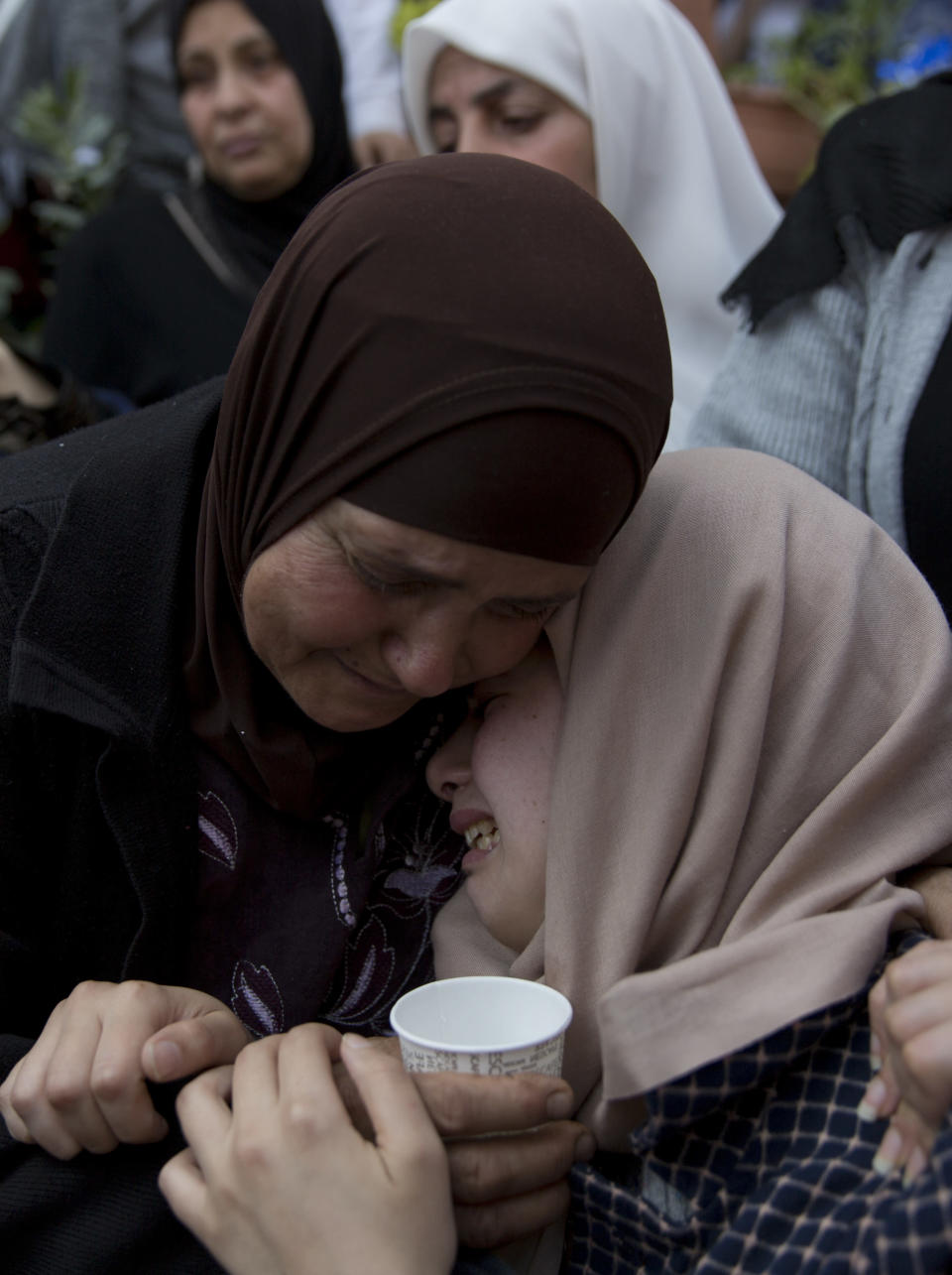 FILE - In this March 21, 2019 file photo, relatives of Palestinian Ahmad Manasra mourn during his funeral in the West Bank village of Wad Fokin, near Bethlehem. In August 2020, Israeli military prosecutors offered three months of community service to a soldier who shot and killed Manasra, an unarmed Palestinian man who exited his vehicle to assist a second motorist who had also been shot -- in a case that has drawn renewed attention to a justice system that Palestinians and human rights activists say has created an atmosphere of impunity. The deal is now being reviewed by the Israeli Supreme Court. (AP Photo/Nasser Nasser, File)