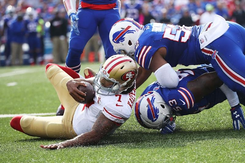Colin Kaepernick (L) of the San Francisco 49ers is brought down by Zach Brown (down) and Preston Brown of the Buffalo Bills on October 16, 2016 (AFP Photo/Tom Szczerbowski)