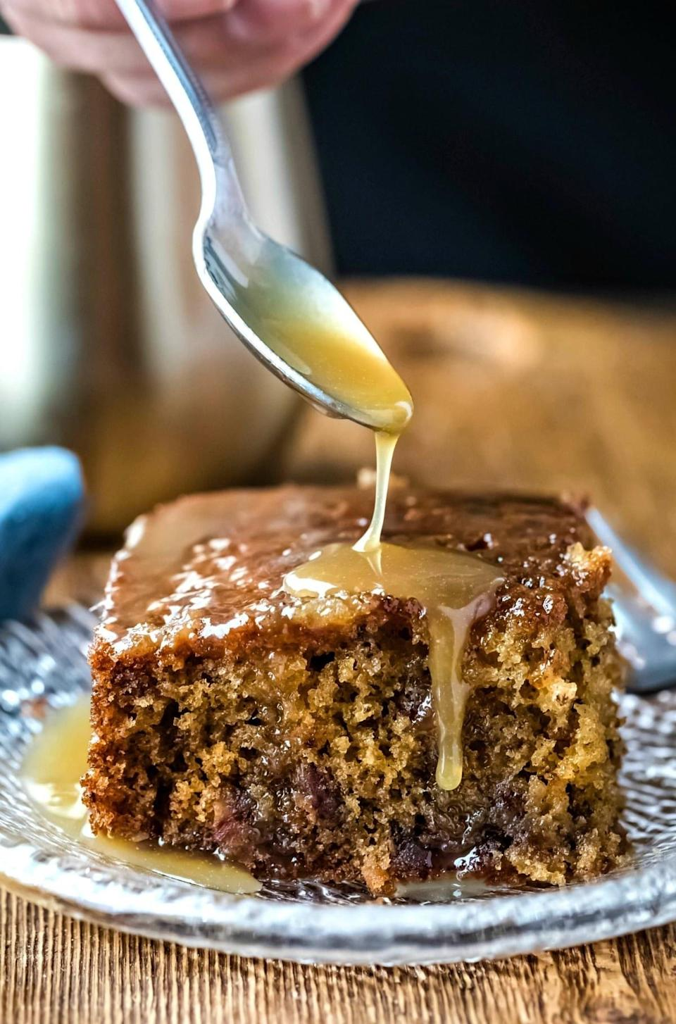 Drizzling caramel onto sticky toffee pudding cake.