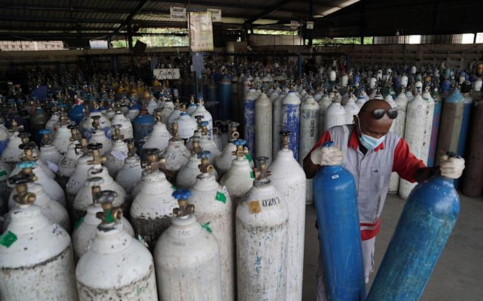 A worker picks up oxygen tanks for hospitals at an oxygen distribution facility in Jakarta, Indonesia, on Tuesday, July 6, 2021. - Dimas Ardian/Bloomberg