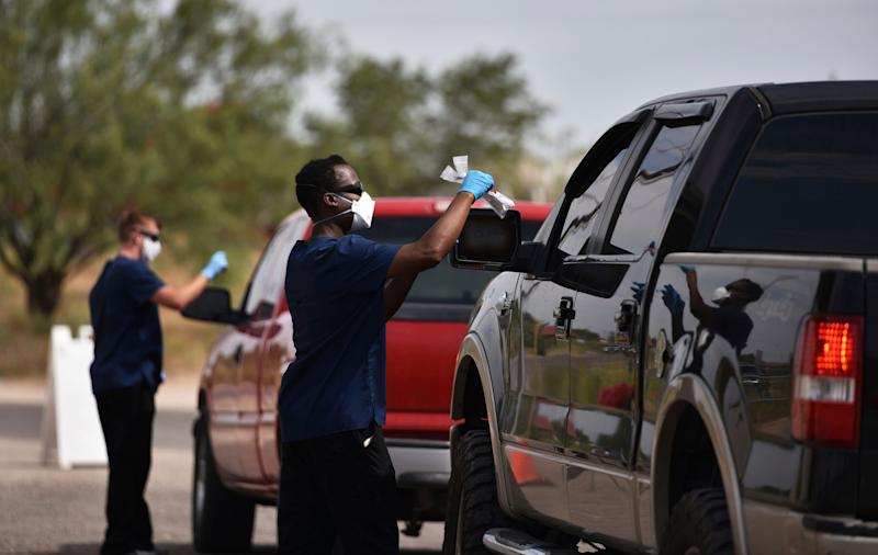 National Guard Specialist Shumirai Tsikada, right, passes a coronavirus testing kit through the window of truck at the West Side Senior Activity Center in Odessa, Texas on Wednesday, July 1, 2020.