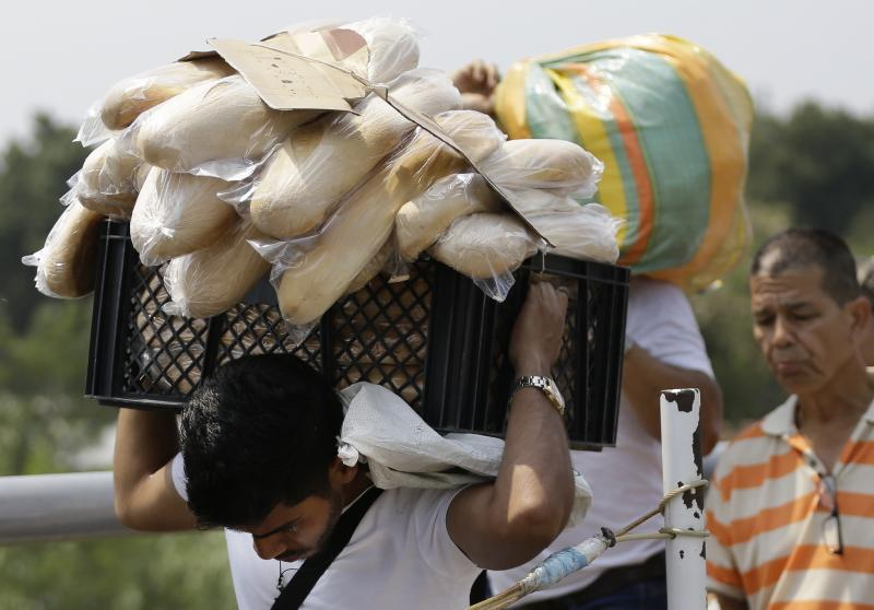 """In this Feb. 4, 2019 photo, a Venezuelan man carries a crate filled with bread back to his country, in La Parada, on the outskirts of Cucuta, Colombia, on the border with Venezuela. Despite Nicolas Maduro's longstanding rejection of outside assistance, opponents of Maduro are hastily putting together plans with U.S. officials to open a """"humanitarian corridor"""" in Cucuta to deliver emergency food and medical supplies. (AP Photo/Fernando Vergara)"""