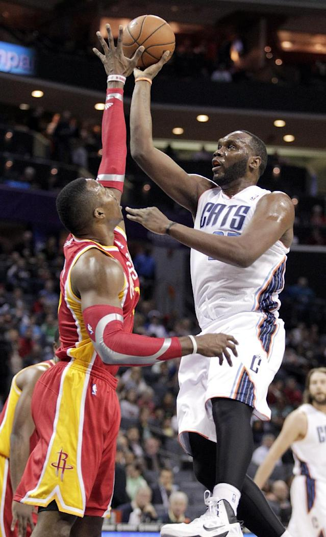 Charlotte Bobcats' Al Jefferson, right, gets his shot off over Houston Rockets' Dwight Howard during the first half of an NBA basketball game in Charlotte, N.C., Monday, March 24, 2014. (AP Photo/Bob Leverone)