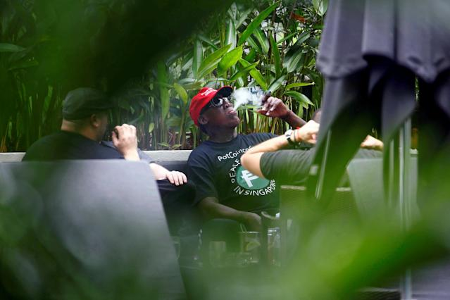 Former U.S. basketball star Dennis Rodman smokes a cigar at the poolside of Regent Hotel in Singapore, June12, 2018. REUTERS/Feline Lim