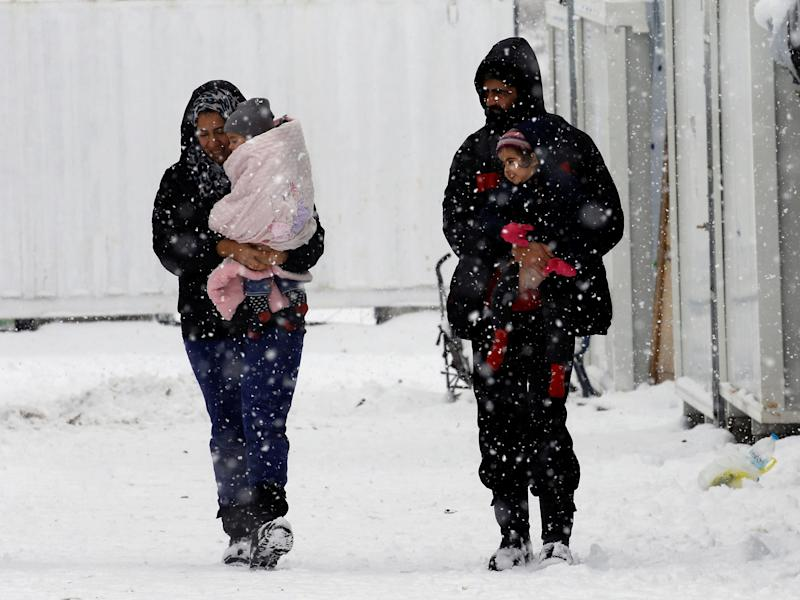 Syrian refugees carry their children through a snow storm at a refugee camp north of Athens, Greece, on 10 January: Reuters