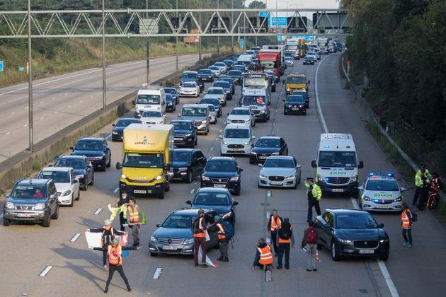 <strong>Insulate Britain climate activists begin to block the anticlockwise carriageway of the M25 between Junctions 9 and 10 as part of a campaign intended to push the UK government to make significant legislative change to start lowering emissions.</strong> (Photo: Mark Kerrison via Getty Images)
