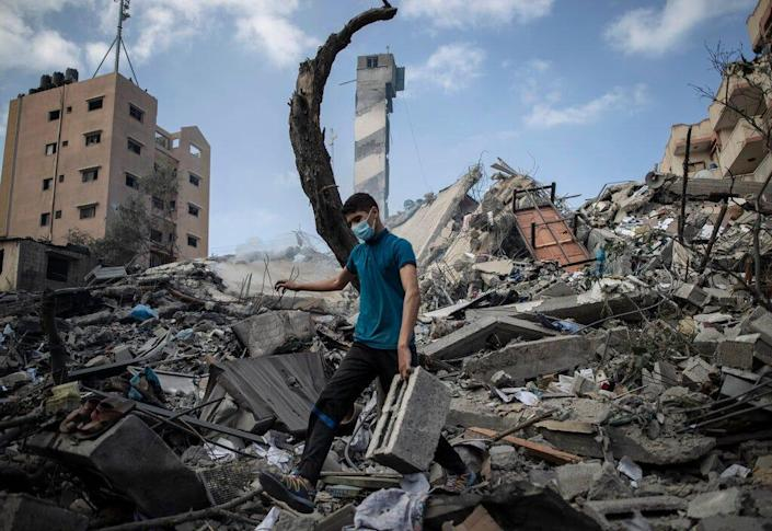 A Palestinian man inspects the damage of a six-story building which was destroyed by an early morning Israeli airstrike, in Gaza City, on May 18, 2021. Israel carried out a wave of airstrikes on what it said were militant targets in Gaza, leveling a six-story building in downtown Gaza City, and Palestinian militants fired dozens of rockets into Israel early Tuesday, the latest in the fourth war between the two sides, now in its second week.