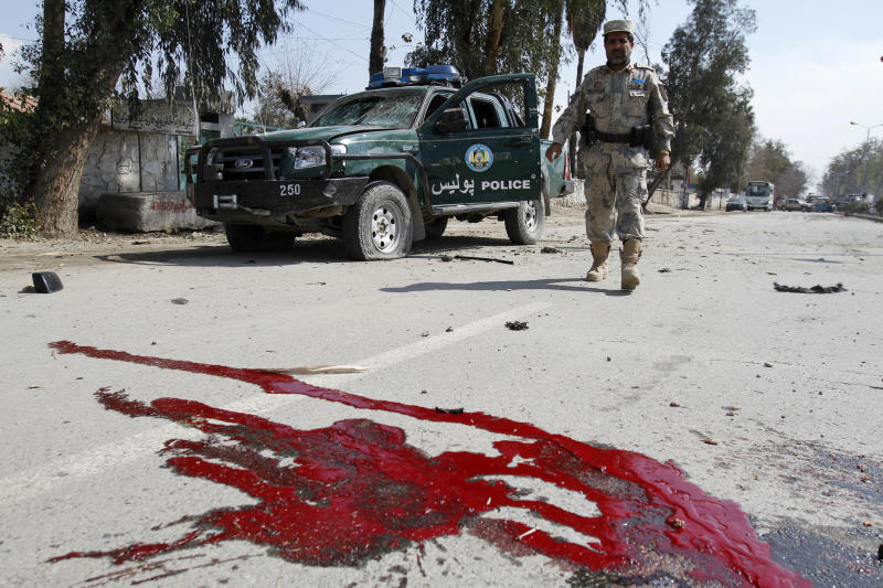 Blood stains are seen in the foreground as Afghan police man arrives at the site of explosion in Jalalabad, Afghanistan, Monday, March, 7, 2011. An Afghan Interior Ministry spokesman says a roadside bomb in the eastern city of Jalalabad has killed two policemen and wounded another 25 people.(AP Photo/Rahmat Gul)