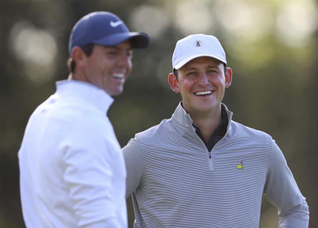 Matt Parziale, right, the U.S. Mid-Amateur champion who works as a firefighter in his hometown in Massachusetts, shares a laugh with Rory McIlroy on the first green during a practice round for the Masters. (AP)