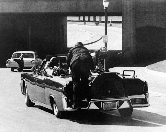 <p>President John F. Kennedy slumps down in the back seat of the presidential limousine as it speeds along Elm Street toward the Stemmons Freeway overpass, after he was fatally shot in Dallas on Nov. 22, 1963. Jacqueline Kennedy leans over the president as Secret Service agent Clinton Hill rides on the back of the car. (Photo: Jim Altgens/AP) </p>