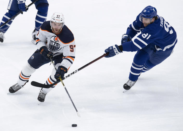 Toronto Maple Leafs center John Tavares (91) chases down Edmonton Oilers center Connor McDavid (97) during the first period of an NHL hockey game Friday, Jan. 22, 2021, in Toronto. (Frank Gunn/The Canadian Press via AP)