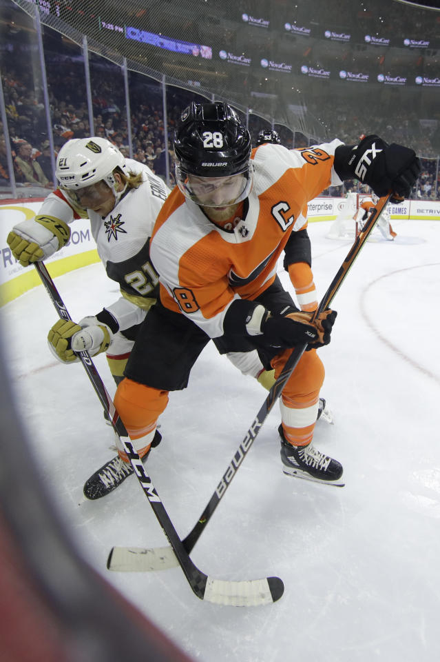 Vegas Golden Knights' Cody Eakin (21) and Philadelphia Flyers right wing Claude Giroux (28) vie for the puck during the first period of an NHL hockey game Monday, Oct. 21, 2019, in Philadelphia. (AP Photo/Matt Rourke)