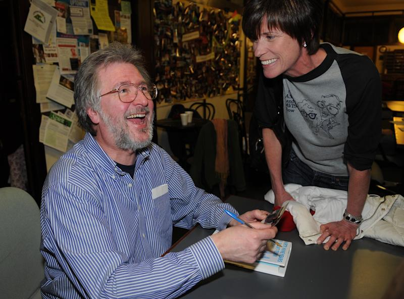 """FILE - In this March 12, 2009 file photo, comedian Tom Davis reminisces with old friend and fan Mary Duffy while signing books in Minneapolis. Davis, a writer and performer who with Al Franken developed some of the most popular skits in the early years of """"Saturday Night Live,"""" died Thursday, July 19, 2012. He was 59. (AP Photo/Dawn Villella, File)"""