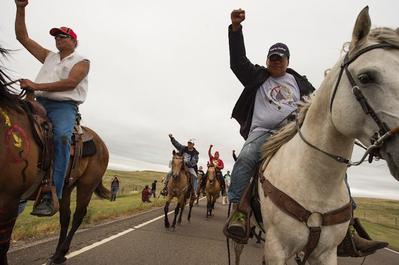 Native Americans ride with raised fists to a sacred burial ground that was disturbed by bulldozers building the Dakota Access Pipeline (AFP Photo/Robyn Beck)
