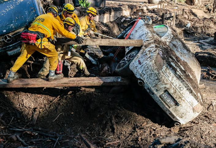 <p>Rescue workers search in an around cars for missing persons after a mudslide in Montecito, Calif., Jan. 12, 2018. (Photo: Kyle Grillot/Reuters) </p>