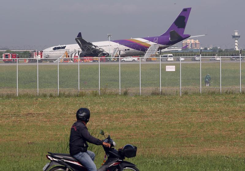 A motorcyclist looks at a damaged Thai Airways Airbus A330-300 at Sunvarnabhumi International Airport in Bangkok, Thailand Monday, Sept. 9, 2013. The plane carrying more than 280 people skidded off the runway while landing Sunday, injuring 14 passengers. After the accident, workers on a crane blacked out the Thai Airways logo on the tail and body of the aircraft. (AP Photo/Apichart Weerawong)