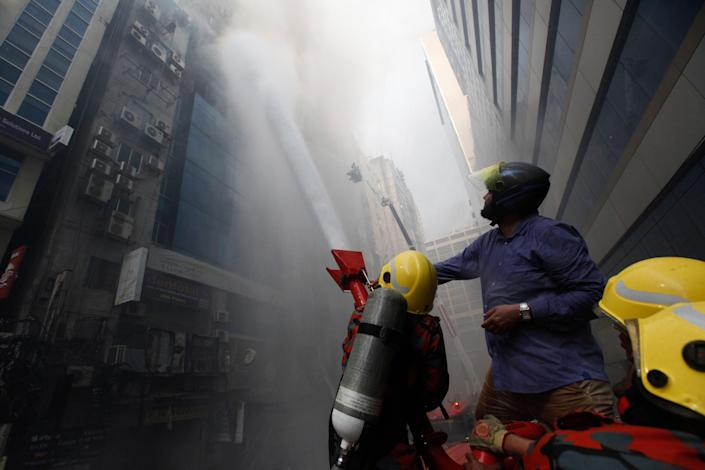 A commuter watches firefighters work to douse a fire in a multi-storied office building in Dhaka, Bangladesh, March 28, 2019. (AP Photo/Mahmud Hossain Opu)