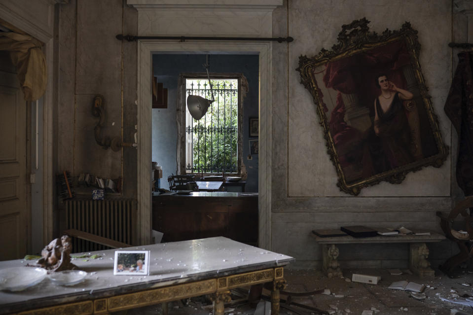 A crooked paint hangs on the wall of the Sursock Palace, heavily damaged after the explosion in the seaport of Beirut, Lebanon, Friday, Aug. 7, 2020. The 150-year-old palace withstood two world wars, the fall of the Ottoman empire, the French mandate and Lebanese independence. After the country's 1975-1990 civil war, it took 20 years of careful restoration for the family to bring the palace back to its former glory. (AP Photo/Felipe Dana)