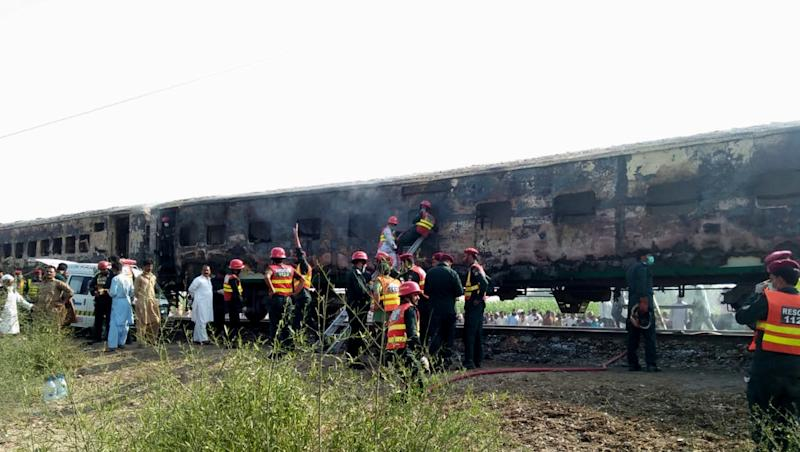 Rescue workers shift the bodies of the victims after a fire engulfed a passenger train near Rahim Yar Khan, Pakistan. Source: EPA/STRINGER.