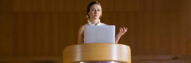 a woman is giving a speech standing at a podium.