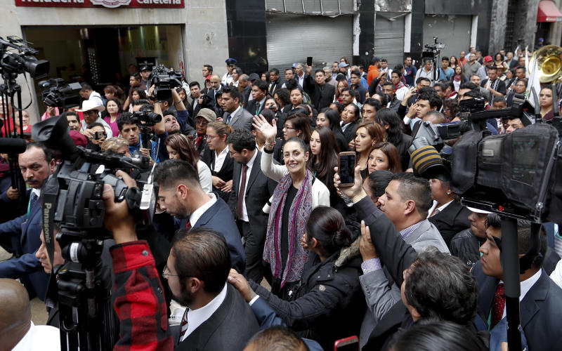 Mexico City's newly sworn-in Mayor Claudia Sheinbaum greets people as she walks to an event in downtown Mexico City, Wednesday, Dec. 5, 2018. The key promises of Sheinbaum, Mexico City's first elected female mayor, include reducing crime and enforcing zoning laws, a hot-button issue in the constantly growing megalopolis where developers routinely build bigger buildings than zoning rules allow. (AP Photo/Eduardo Verdugo)
