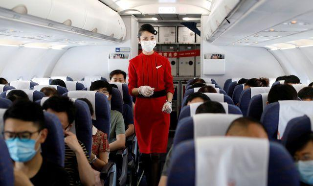 Flight attendant in the aisle of a plane amongst rows of passengers